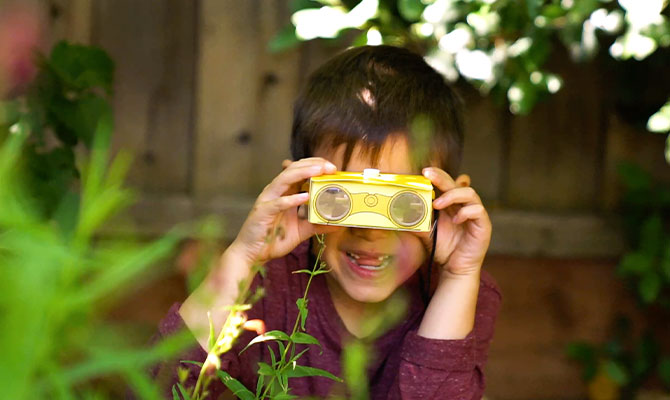 child with crafted binoculars