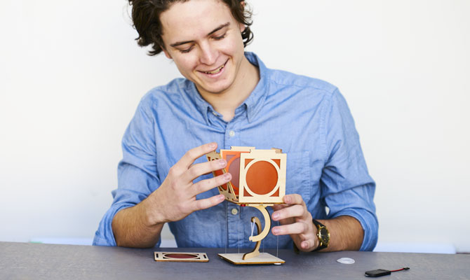 A teen boy assembles an artistic-looking lamp made of laser-cut wood and brightly colored paper.