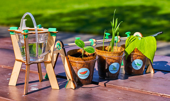 A row of three small plant pots sit in a line on an outside table. They are connected by a drip irrigation system attached to a cup of water.