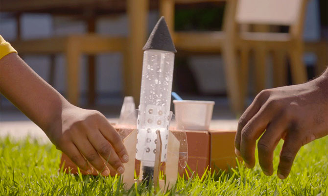 A plastic bottle rocket sits in the grass with an orange Tinker Crate box behind. A child's hand holds the rocket while an adult's hand reaches in to help.