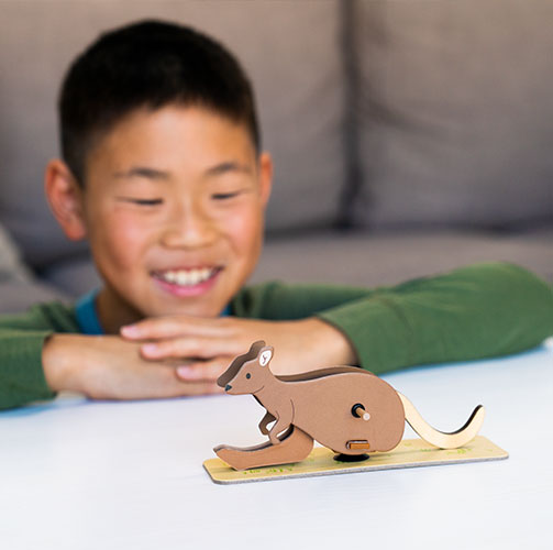 A child enjoying with a wooden kangaroo toy from an Atlas Crate geography box