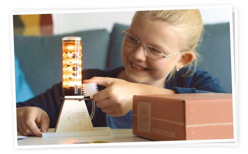 Happy child with diy lava lamp from Tinker Crate monthly STEM kit