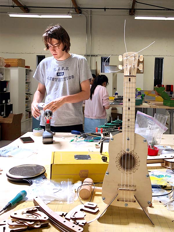 A workshop with fully assembled ukulele from Eureka monthly STEM kit for adults