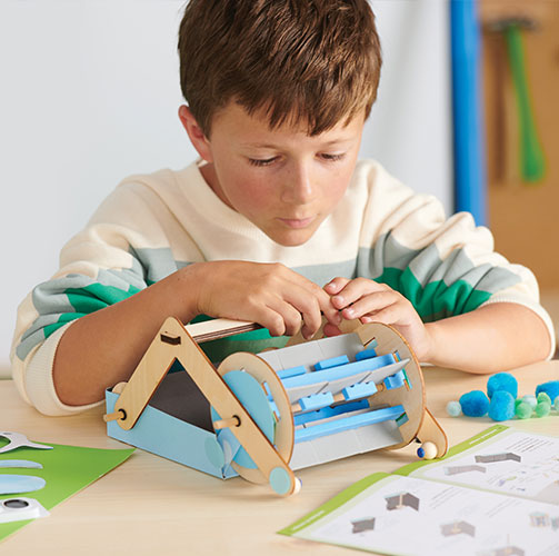 A child building a DIY engineering project from a Kiwi Crate STEM box