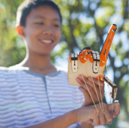 Young engineer with a DIY mechanical hand project from a Tinker Crate engineering box